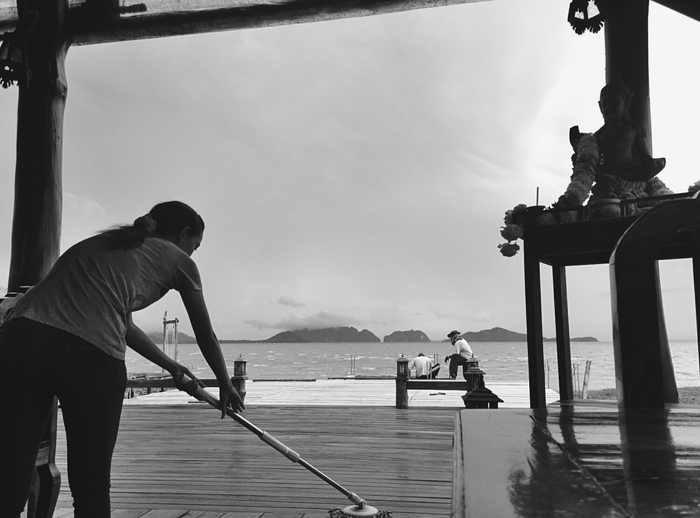 Two men building and a lady cleaning at a hotel in Old Town Koh Lanta, Thailand.