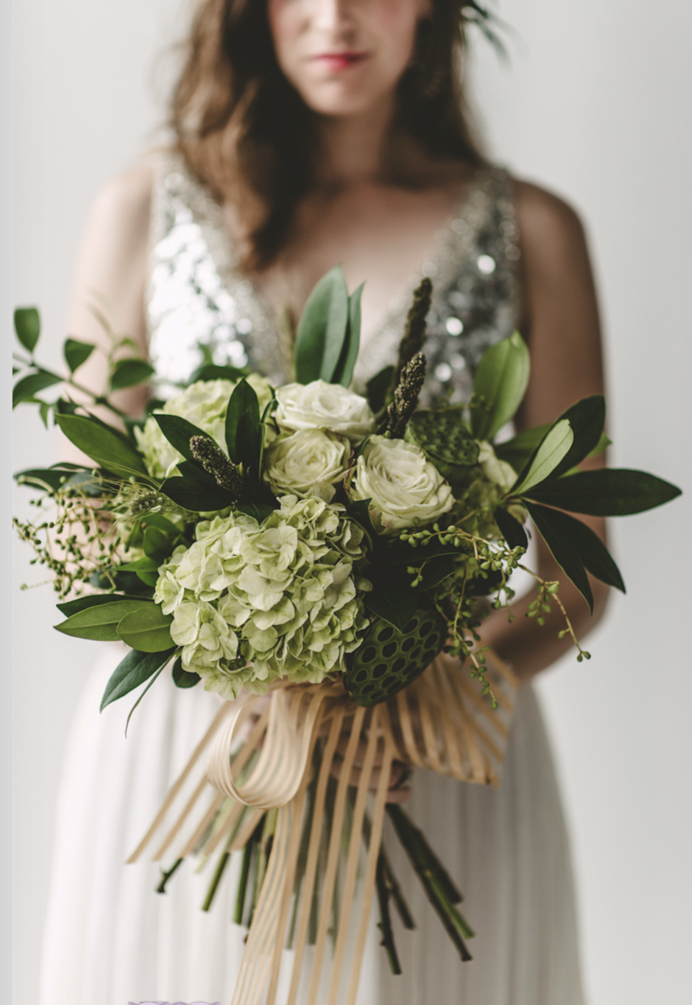 Big bridal bouquet featuring whites and greenery.