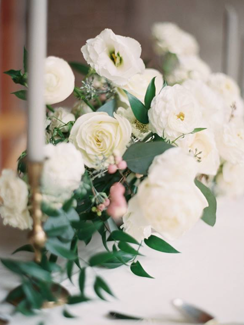 White florals with touches of greenery mixed with brass candlesticks are the perfect table decor for Spring.