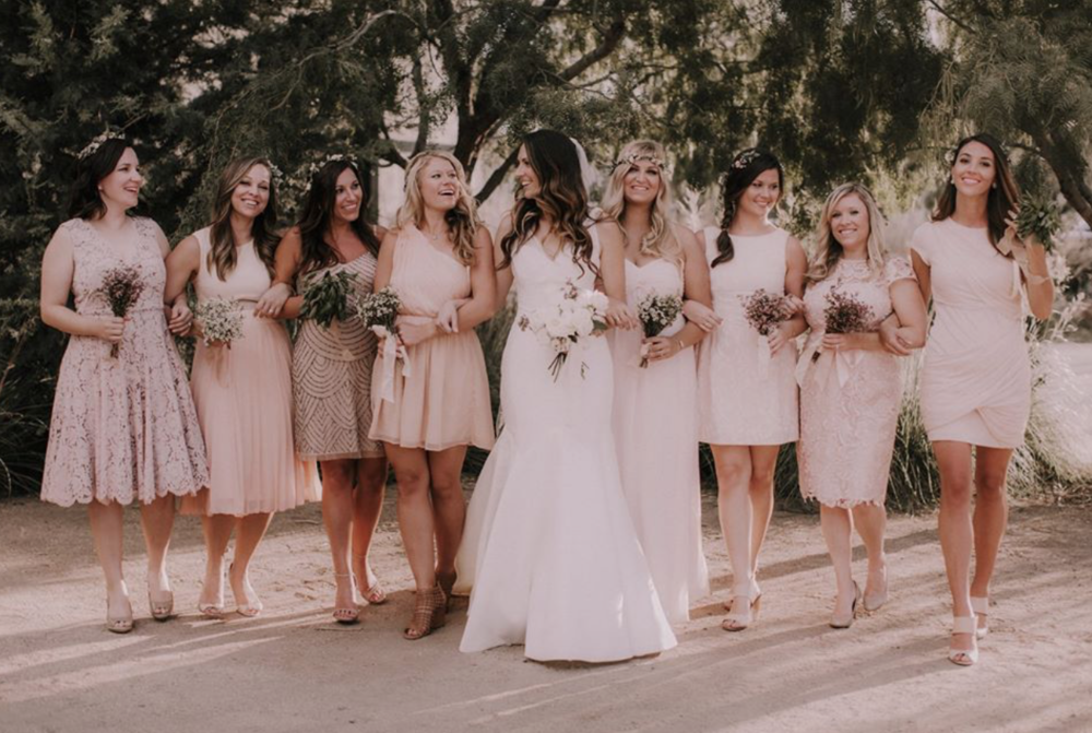 A stunning bridal party in all blush dresses with wildflower bouquets.