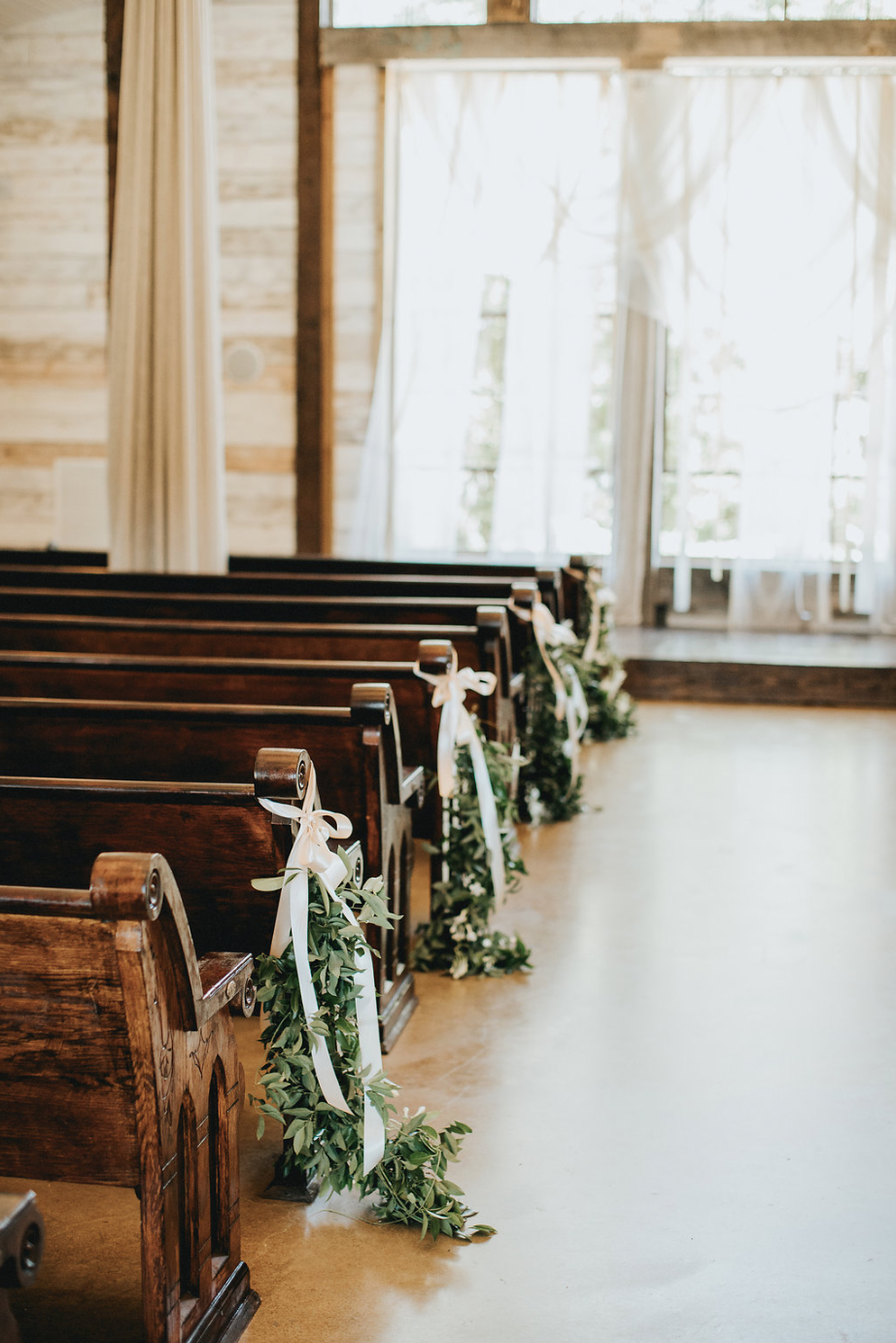 Pews draped with greenery by Maxit Flower Design in Houston, TX