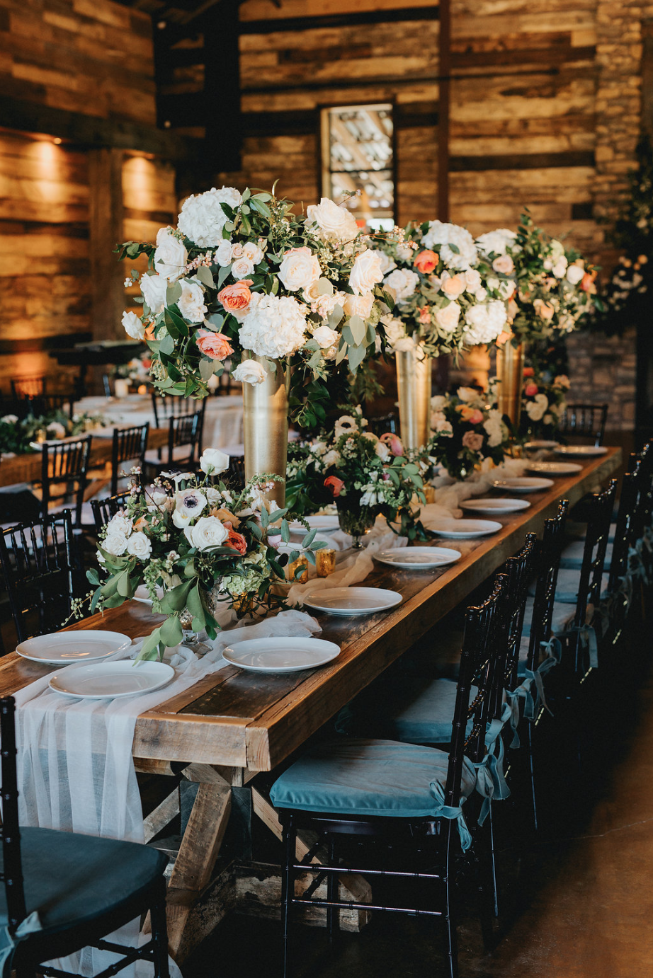 Wooden table with mixed heights arrangements by Maxit Flower Design in Houston, TX
