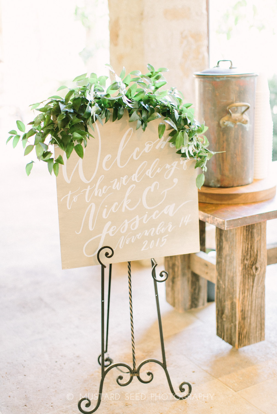 Calligraphy welcome sign draped with greenery by Maxit Flower Design in Houston, TX.