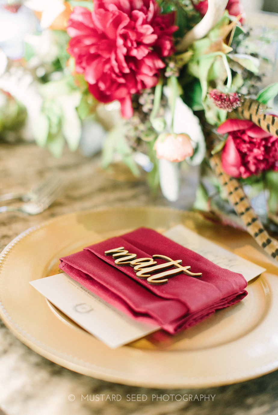 Guest place setting with wooden laser cut name and floral arrangement.