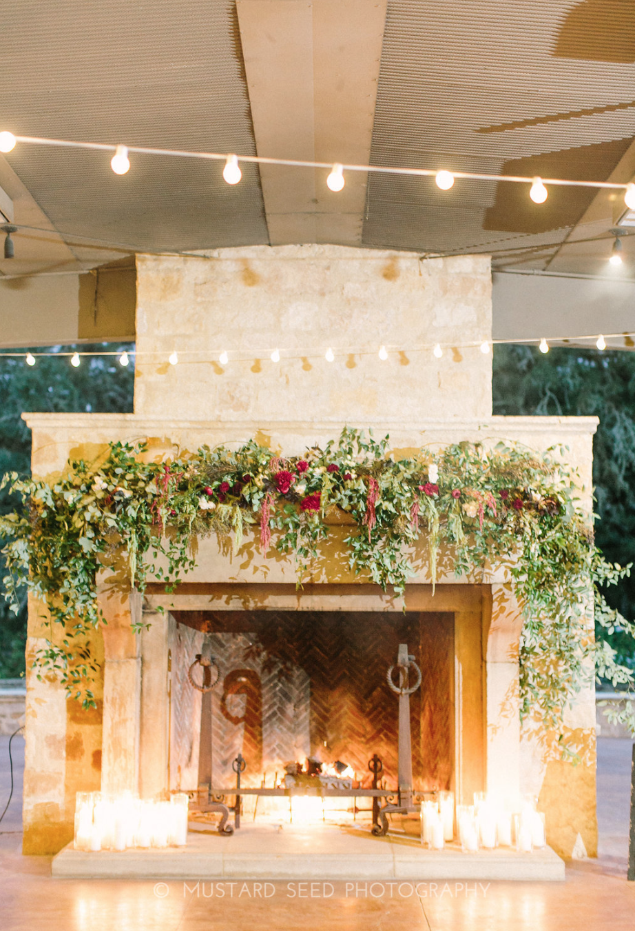 Fireplace with hanging greenery and candles by Maxit Flower Design in Houston, TX.