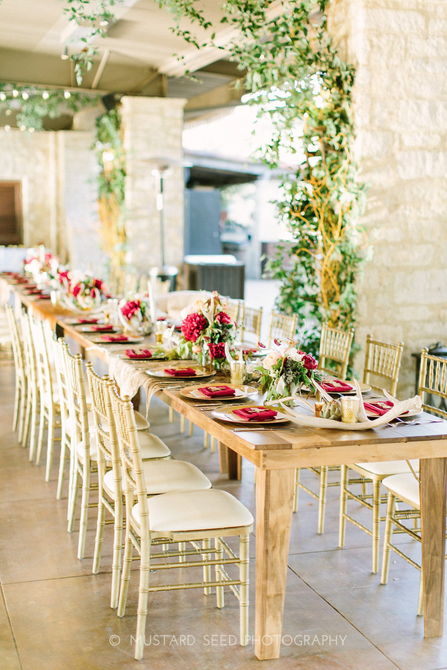Wooden Head Table with floral arrangements and greenery