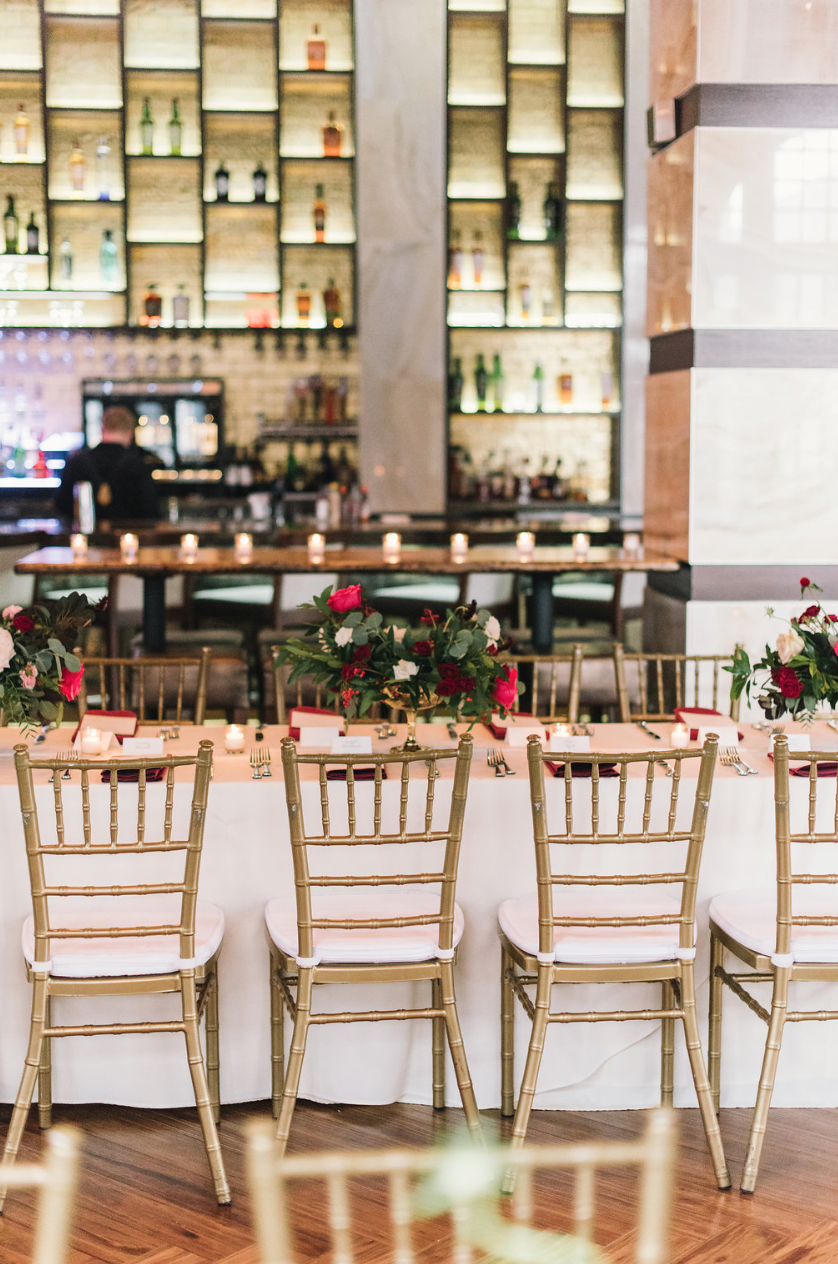A wide shot of the table with the spirits in the background. Gold chivari chairs with red flower arrangements.