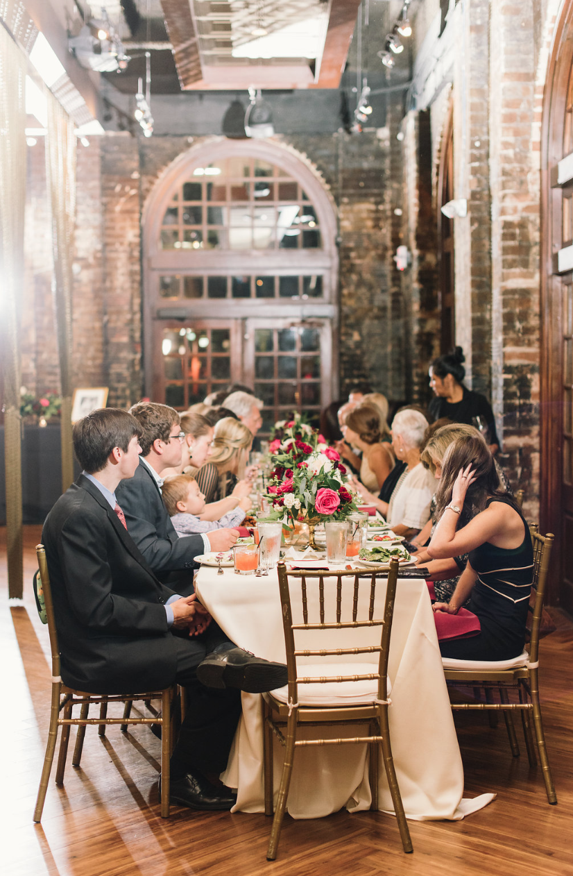 The guests enjoying each others company. Ivory tablecloths with brick background and red based arrangements.