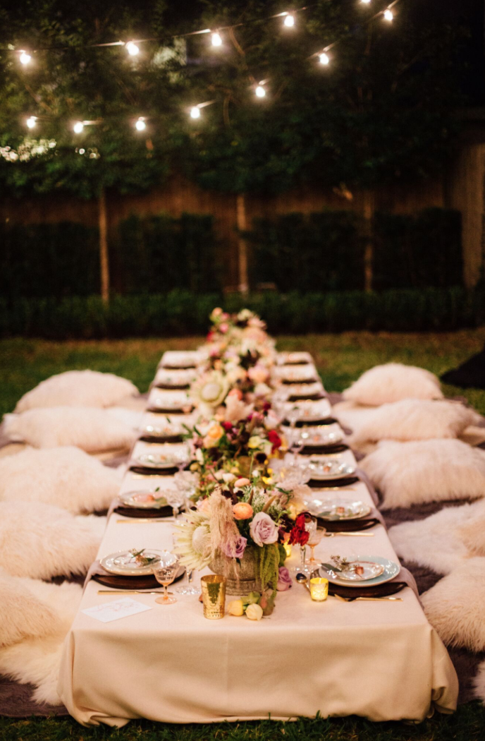 Backyard Bohemian Dinner party with lawn-level table and fluffy pillows. Flowers by Maxit Flower Design in Houston, Texas.