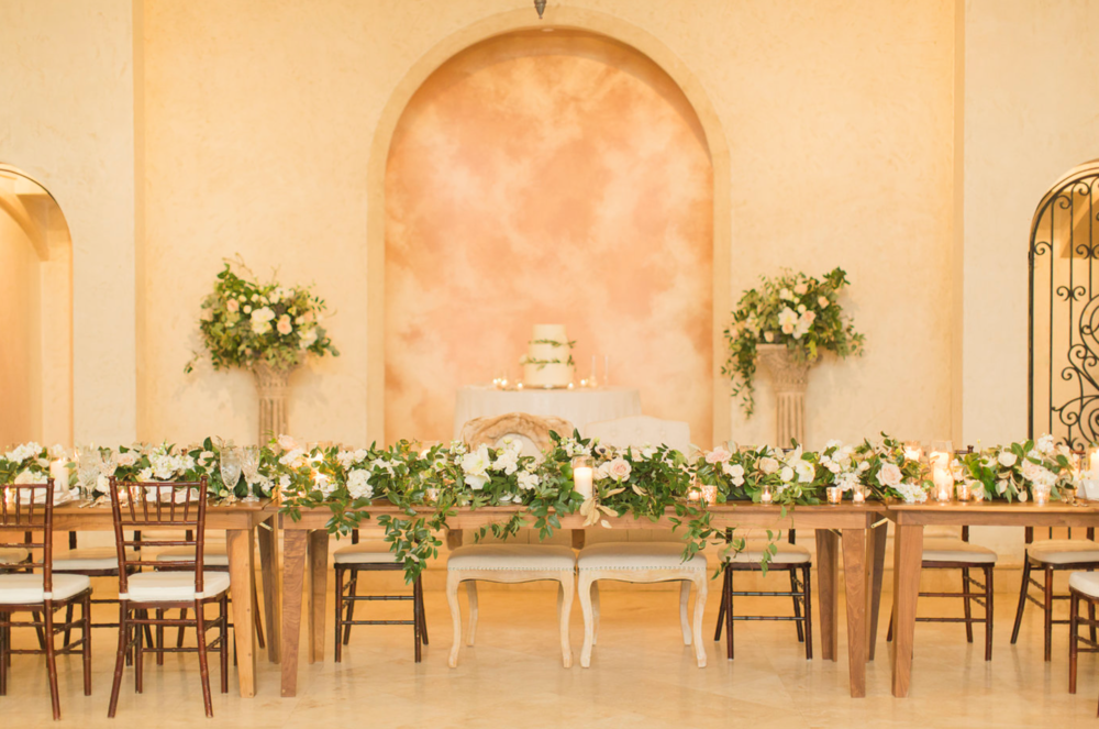Head table at the Bell Tower with greenery and rose garland.