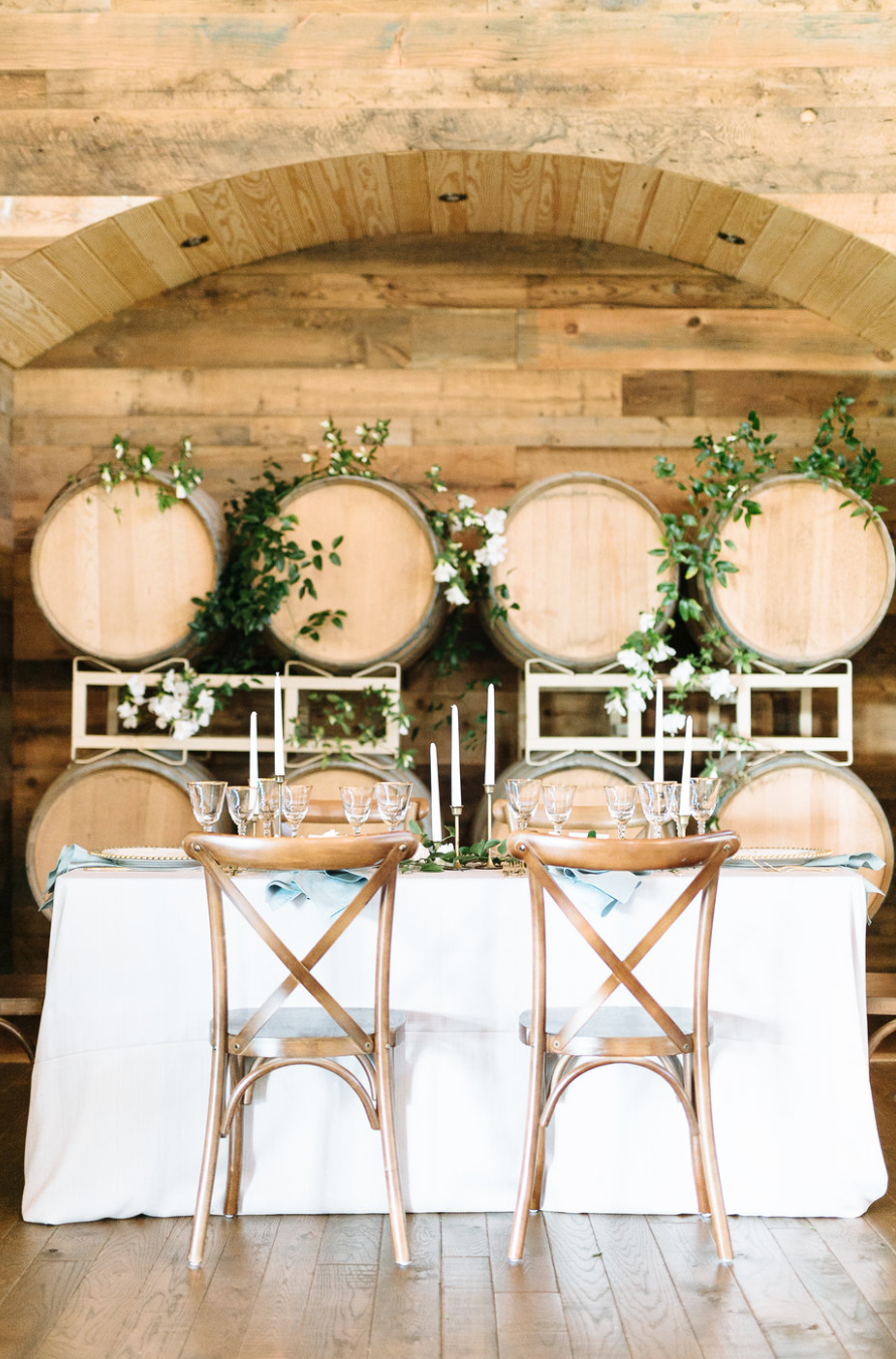 wedding table with wine barrels and greenery by maxit flower design houston texas