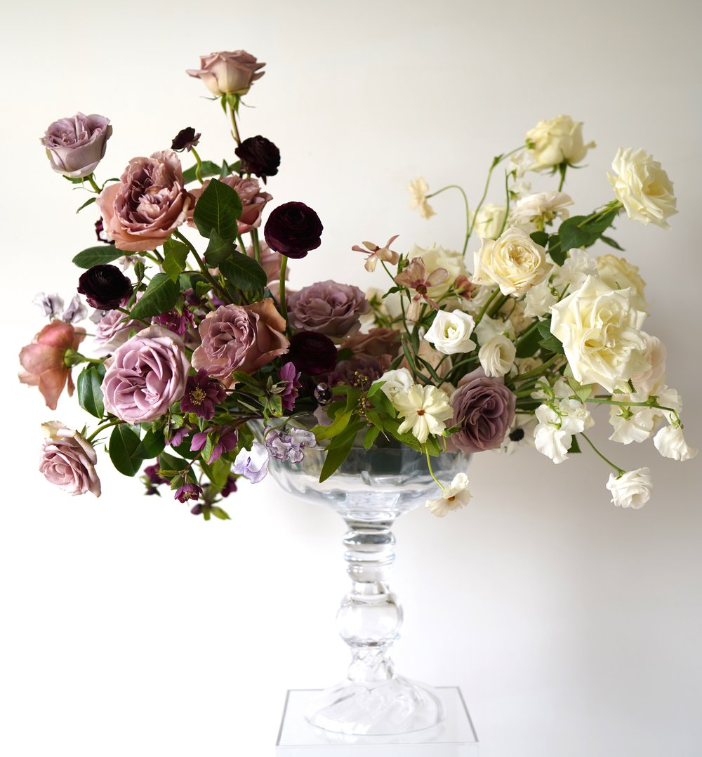 Centerpiece with plumb, mauve, blush, white flowers. Including sweet peas, butterfly ranunculus, hellebores, garden roses, roses, and spray roses. Clear glass vase. Maxit Flower Design