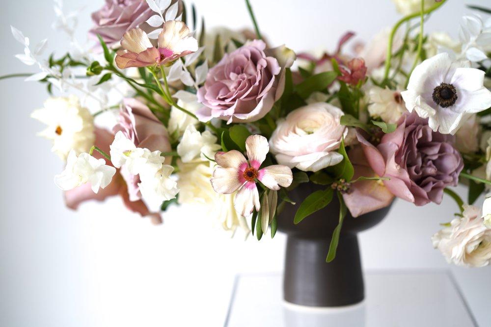 Black modern vessel with a garden style arrangement. Mauve, purple, ivory colored flowers. Maxit Flower Design.
