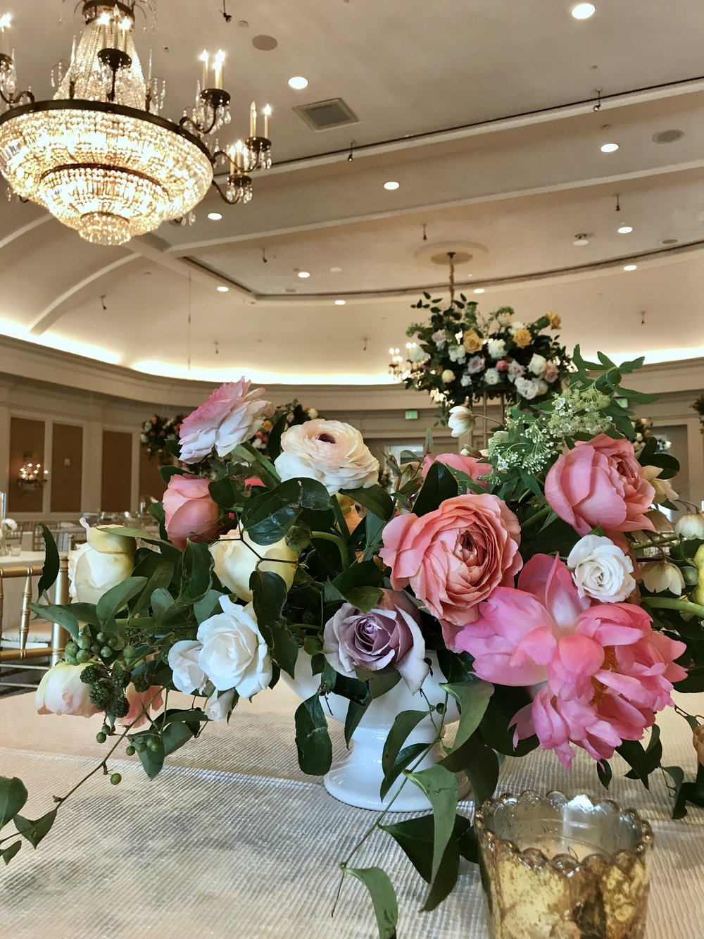 Compote arrangement of lush, premium flowers. White ceramic container with coral charm peonies, garden roses, roses, ranunculus, spirea, black berries and smilax. Keely Thorne Event Planning, River Oaks Country Club, Maxit Flower Design