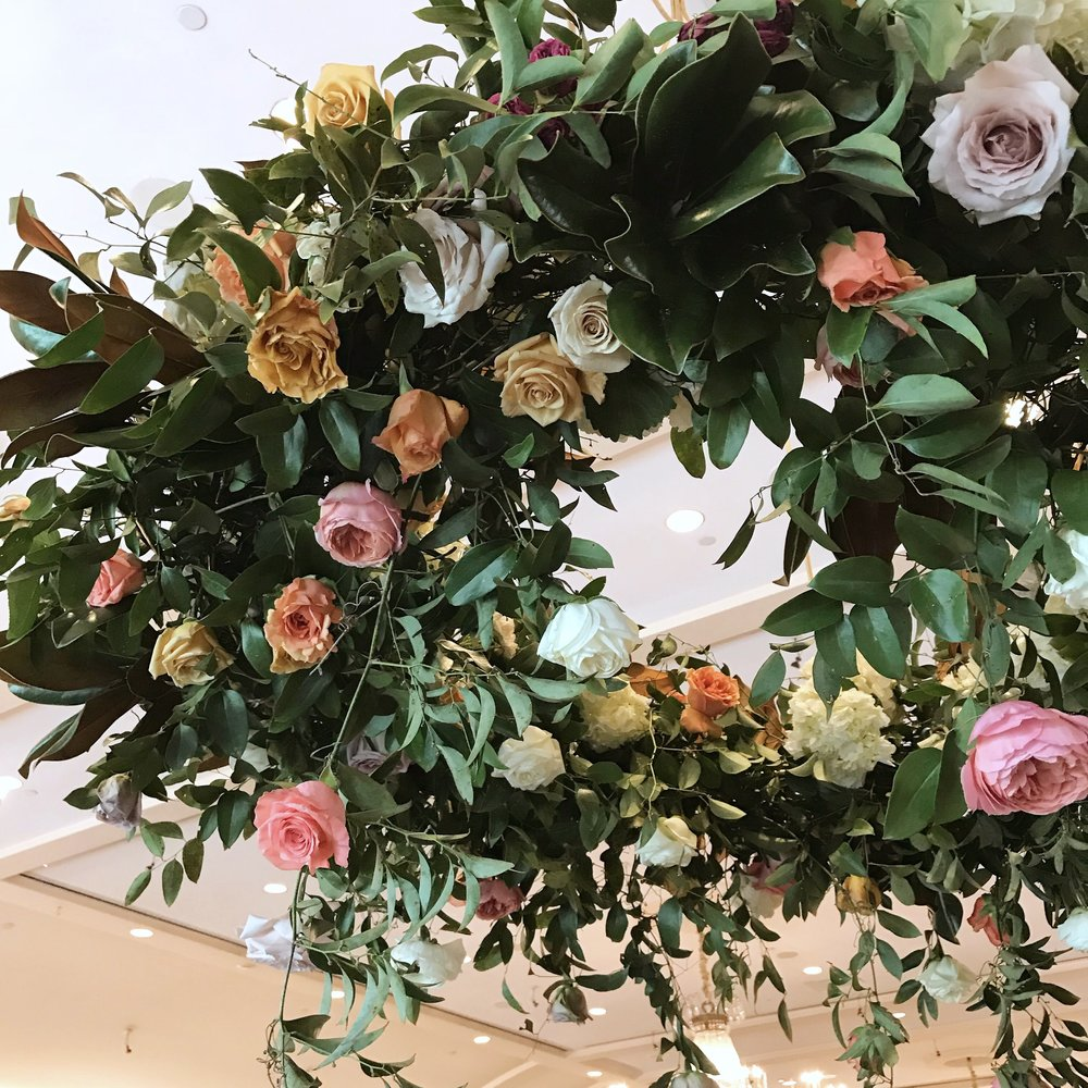 Hanging floral chandelier  with coral charm peonies, garden roses, roses, ranunculus, spirea, black berries and smilax.  Keely Thorne Event Planning, River Oaks Country Club, Maxit Flower Design