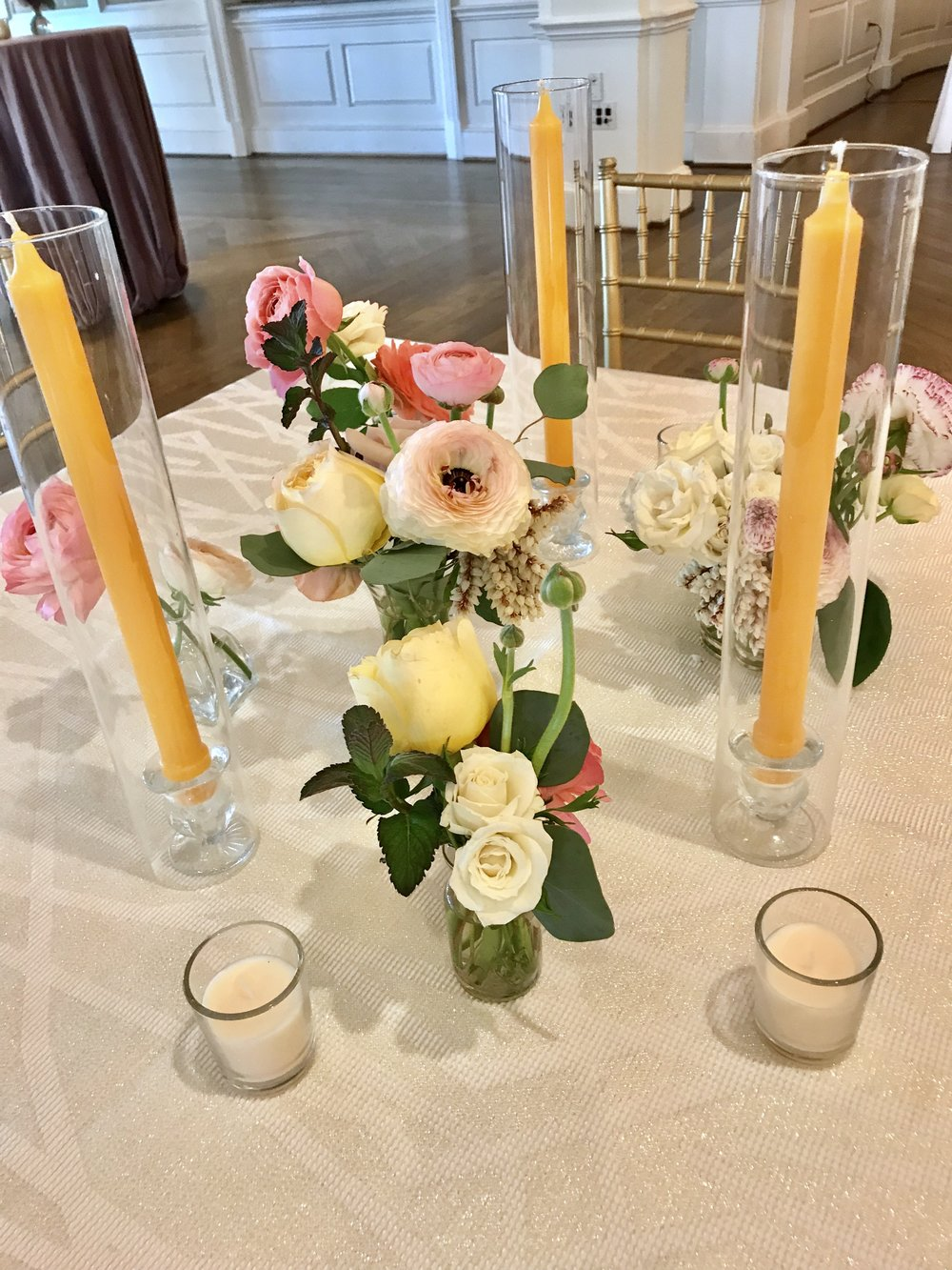 Small vases with taper candles.  With coral charm peonies, garden roses, roses, ranunculus, spirea, black berries and smilax. Keely Thorne Event Planning, River Oaks Country Club, Maxit Flower Design