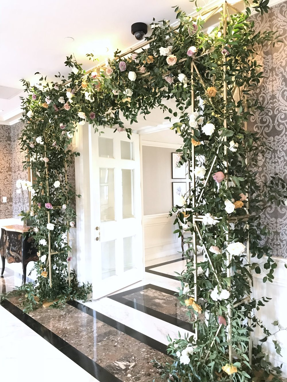 Entry arch covered in flowers, with coral charm peonies, garden roses, roses, ranunculus, spirea, black berries and smilax. Keely Thorne Event Planning, River Oaks Country Club, Maxit Flower Design