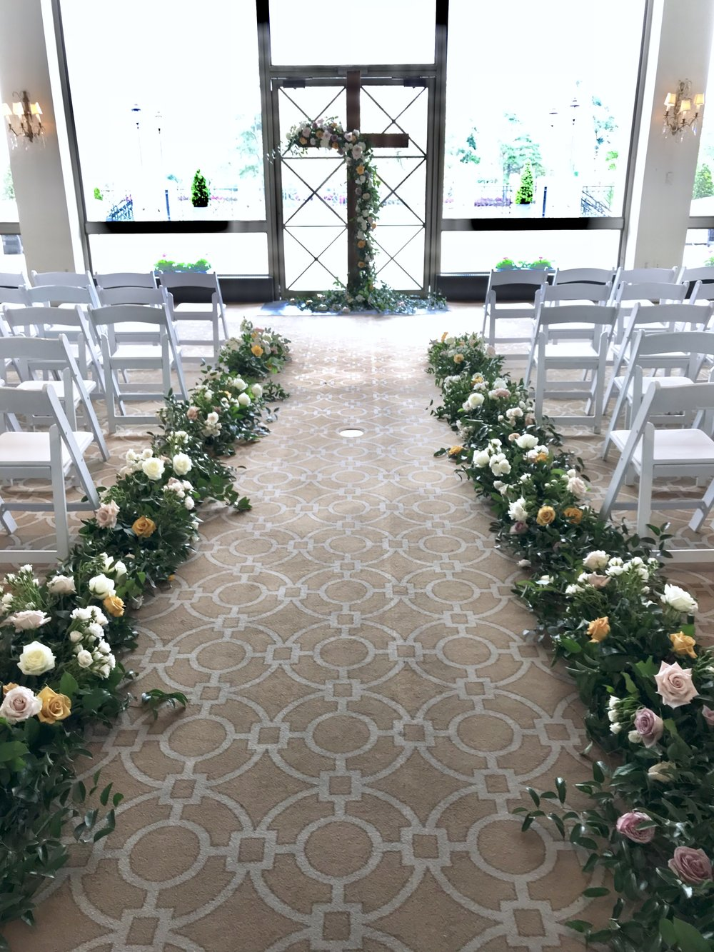 Cross alter with coral charm peonies, garden roses, roses, ranunculus, spirea, black berries and smilax. Aisle covered in blooms. Keely Thorne Event Planning, River Oaks Country Club, Maxit Flower Design