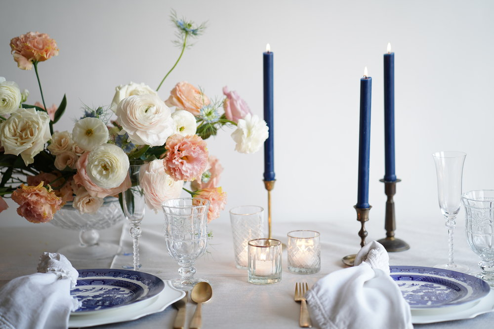 Navy taper candles were the focal point in this design. Peach florals, white chargers and white linens give it a clean look. Flowers and table styling by Maxit Flower Design