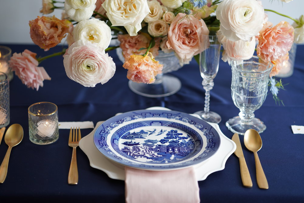 Blue and white China with navy linens. Peach and white florals. Flowers and styling by Maxit Flower Design