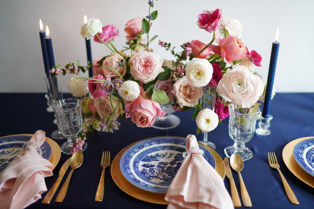 Gold charger for a more formal look. Navy taper candles and navy linens together give such a cohesive look. Pops of pink garden style arrangements. Flowers and styling by Maxit Flower Design