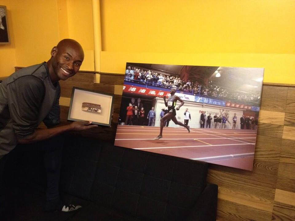 Bernard Lagat poses with an autographed piece of The Armory's track, which will be raffled off at Saturday's NYRR Millrose Games. Enter to win here.