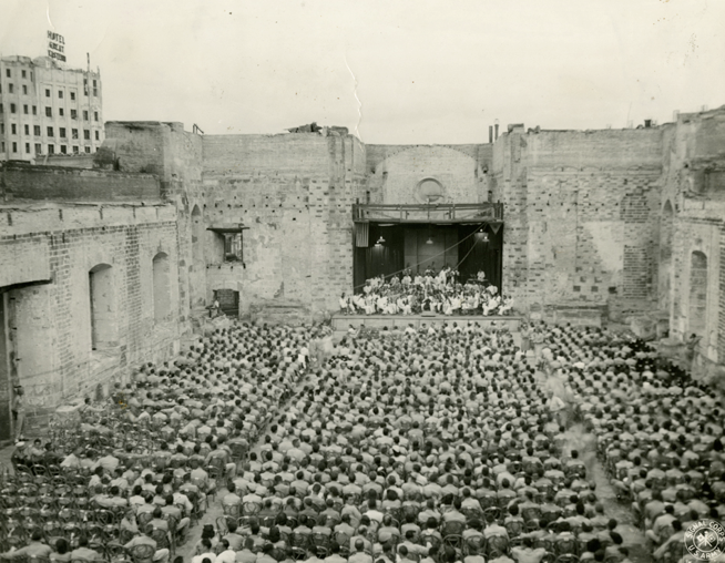 "Gelatin Silver Print: U.S. Army Signal Corps, May 9, 1945. ""Liberation Concert"" with Herbert Zipper conducting the Manila Symphony Orchestra in the ruins of Santa Cruz Church, Manila, The Philippines. From the collection of The Herbert Zipper Archives, Crossroads School for Arts & Sciences."