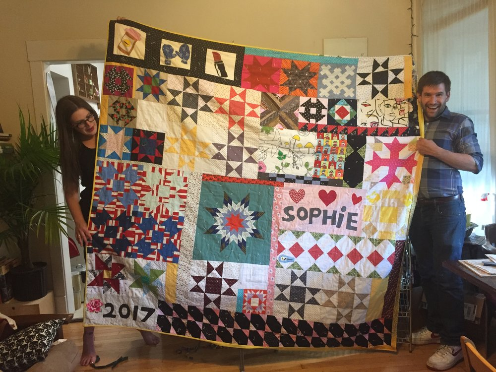 Sophie and Luke hold up the QUILT.
