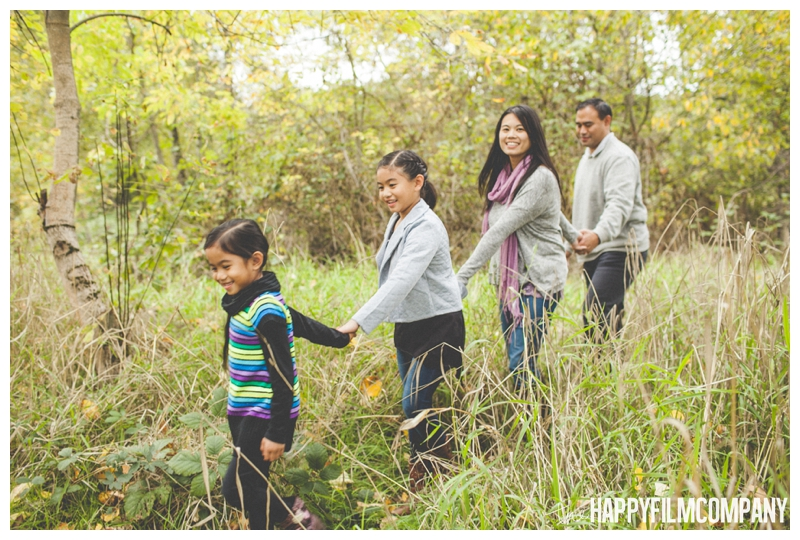 family holding hands and walking through field - Seattle Autumn Family Photos — Playing in the Leaves at Black River Riparian Forest and Wetland - the Happy Film Company