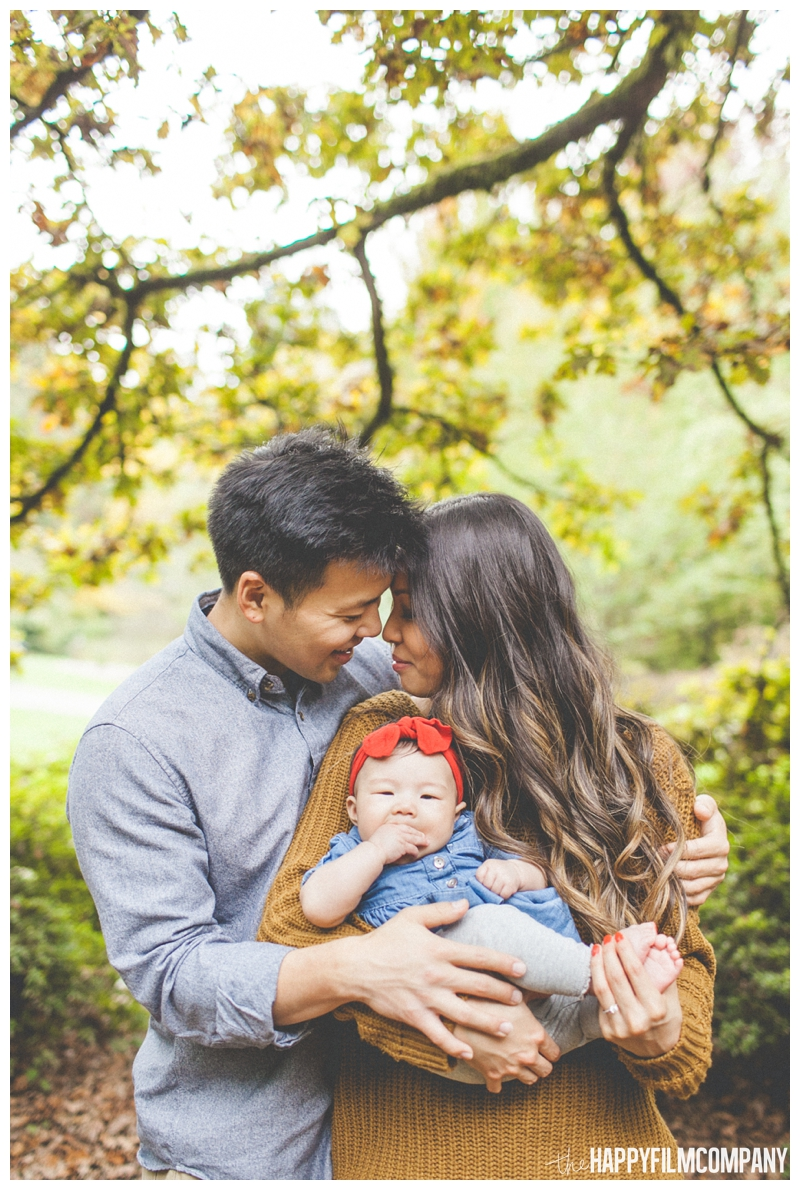 mom and dad holding baby cuddling autumn leaves  - Seattle Family Holiday Portraits - the Happy Film Company