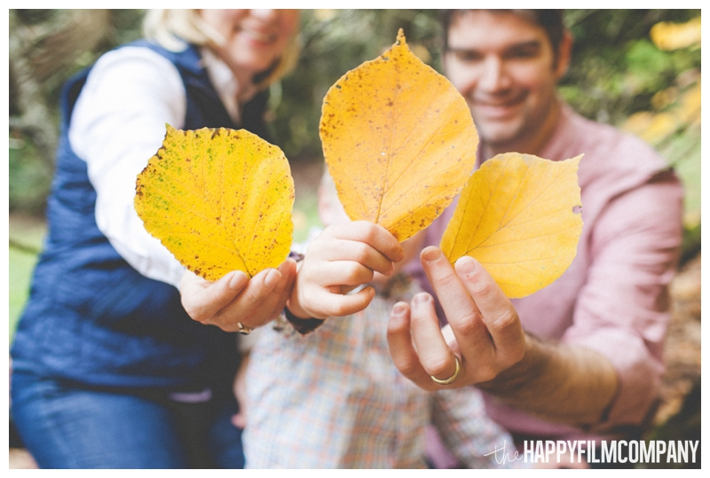 family holding orange leaves  - the Happy Film Company - Seattle family holiday photo shoots - Arboretum