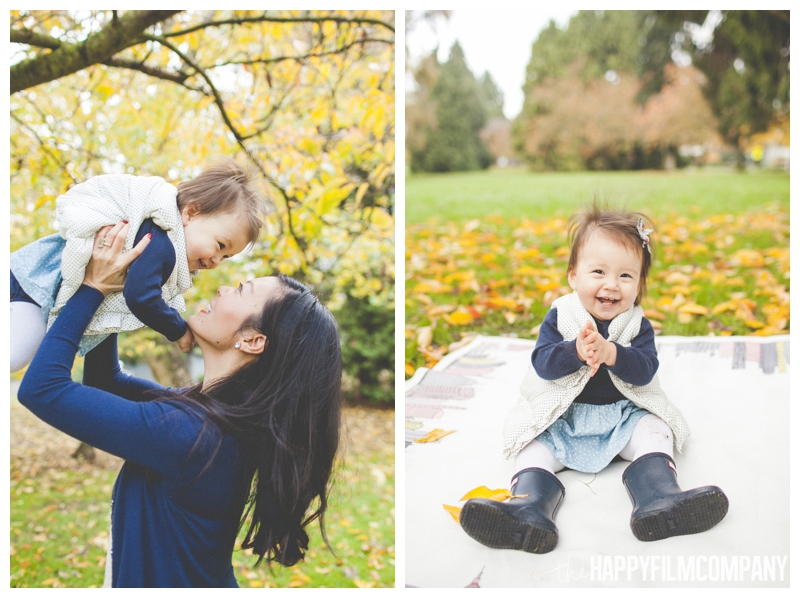 holding baby in air for kisses little girl sitting on blanket  - the Happy Film COmpany - Greenlake Park Seattle Family HOliday Photos