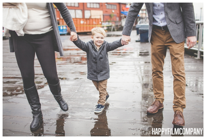 cute little boy standing in rain holding hands  - Seattle Waterfront Family Holiday Photos - the Happy Film Company