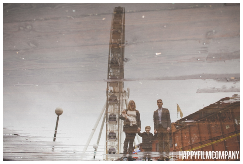 family reflection in rain puddle - Seattle Waterfront Family Holiday Photos - the Happy Film Company