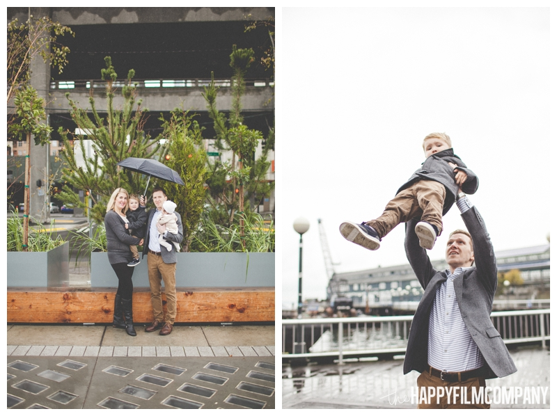 dad throwing son in the air family photos in the city  - Seattle Waterfront Family Holiday Photos - the Happy Film Company
