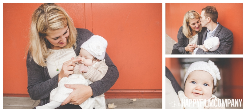 mother holding baby with red background  - Seattle Waterfront Family Holiday Photos - the Happy Film Company