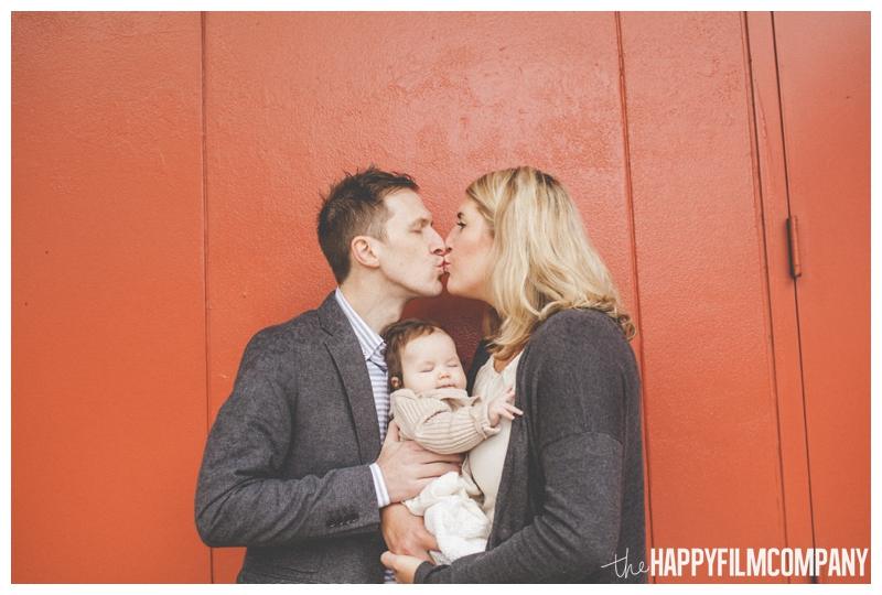 mom and dad kissing over baby's head  - Seattle Waterfront Family Holiday Photos - the Happy Film Company