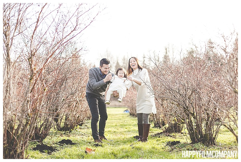 family pictures at blueberry farm in winter  - the Happy Film Company - Winter Family Portraits Seattle swinging little girl