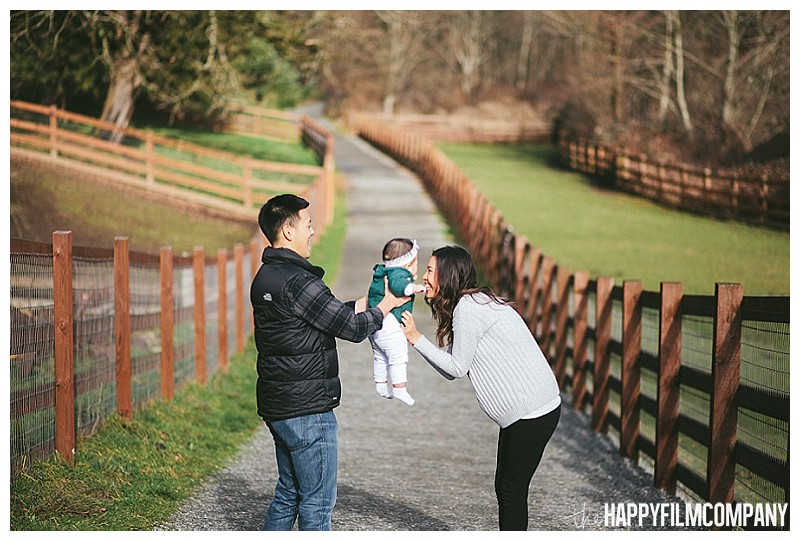 farm family photos swinging baby in air next to fence  - the Happy Film Company - Winter Seattle Family Portraits