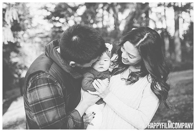 black and white family photos laughing smiling at baby holding little girl  - the Happy Film Company - Winter Seattle Family Portraits