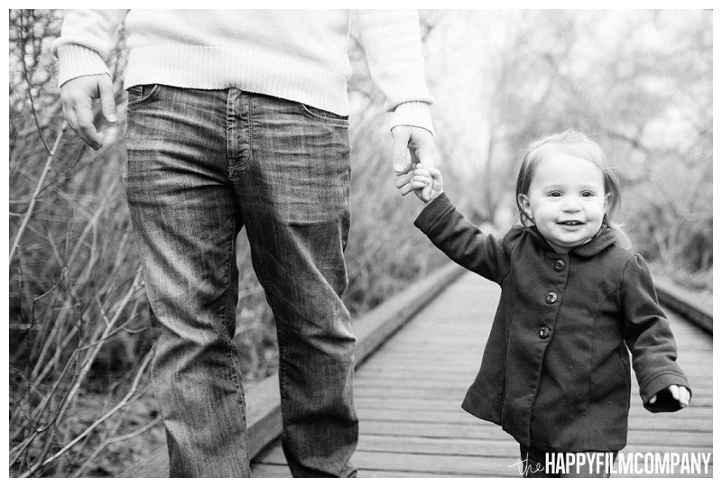 father daughter portrait holding hands walking on boardwalk  - the Happy Film Company - Seattle Mini Family Photo Shoot - Juanita Bay park