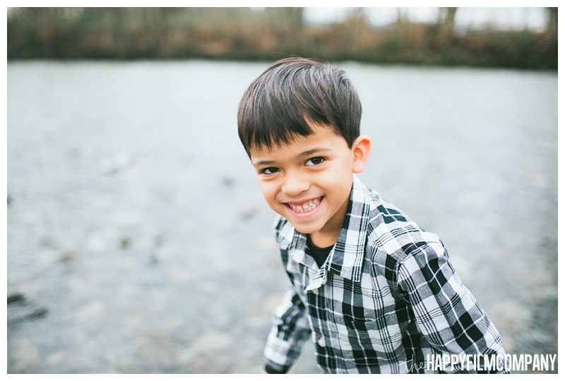 happy little boy black and white plaid shirt smiling by river  - the Happy Film Company - Seattle Family Photos