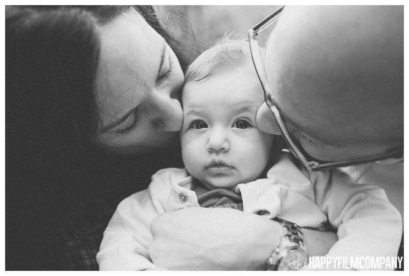 black and white family photo kissing baby on cheeks  - the Happy Film Company - Seattle PEPS Group Family Portraits