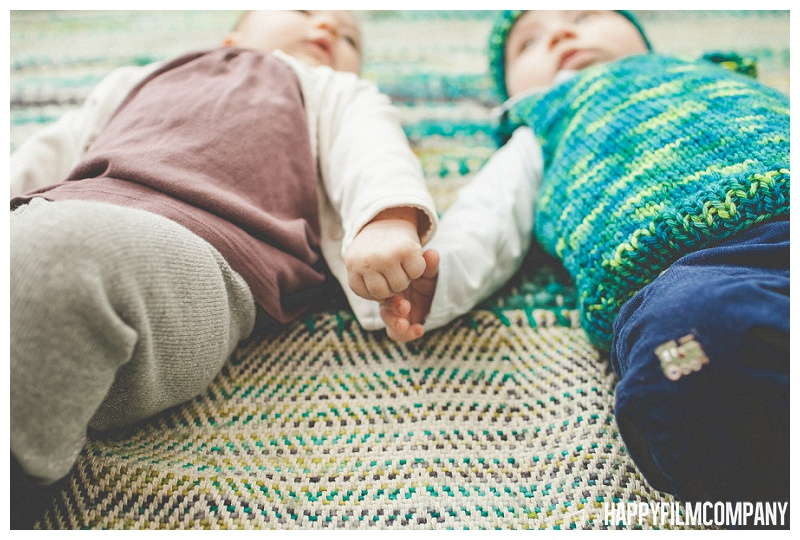 babies holding hands lying on back on teal blanket  - the Happy Film Company - Seattle PEPS Group Family Portraits