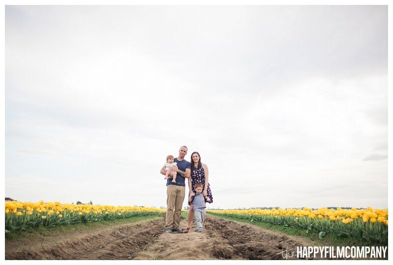 family standing in tulip field cloudy sky yellow flowers - the Happy Film Company - Seattle Family Portraits