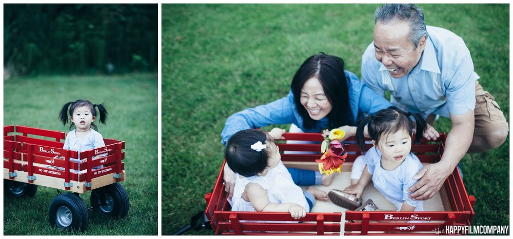Little girls on a red cart - the Happy Film Company - Seattle Family Photos