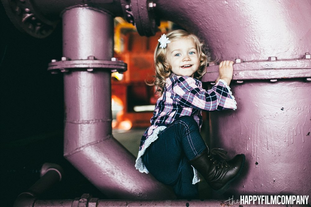 Little girl sitting at the uncover engine park - the Happy Film Company - Seattle Family Photos