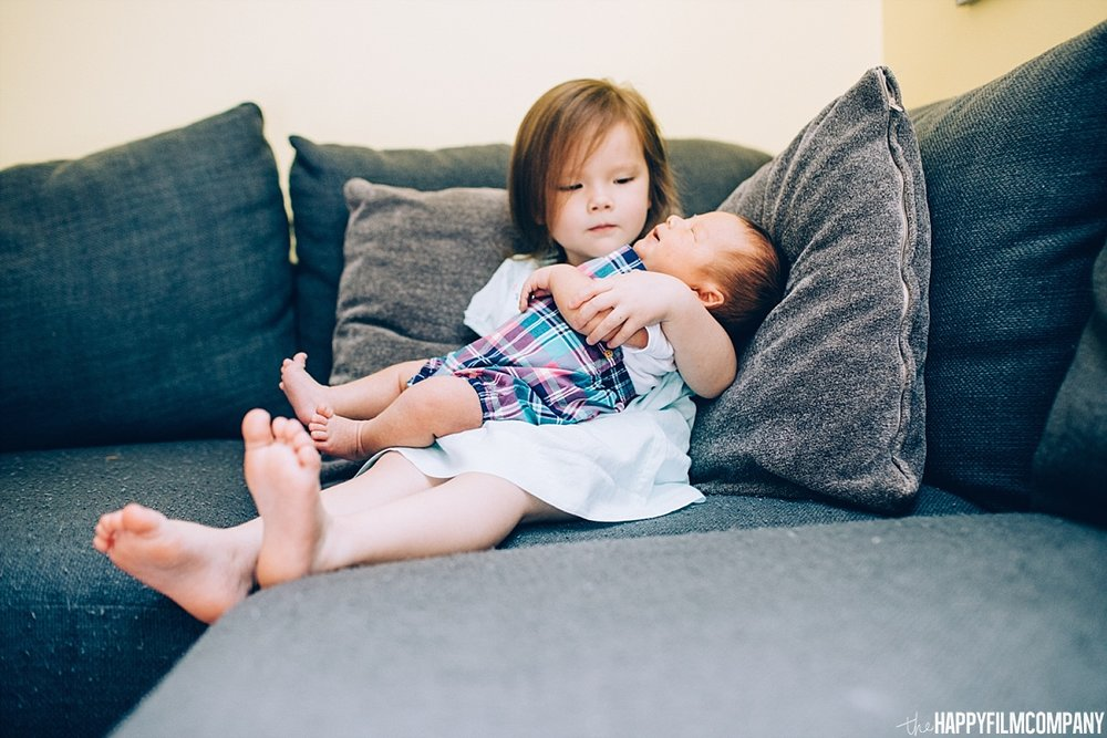 Little girl and newborn baby brother sitting in the couch - the Happy Film Company - Seattle Family Photos