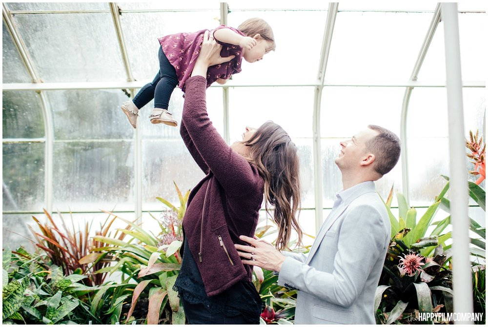 the Happy Film Company - Seattle Family Photos - Volunteer Park Conservatory - holding baby up in the air in greenhouse