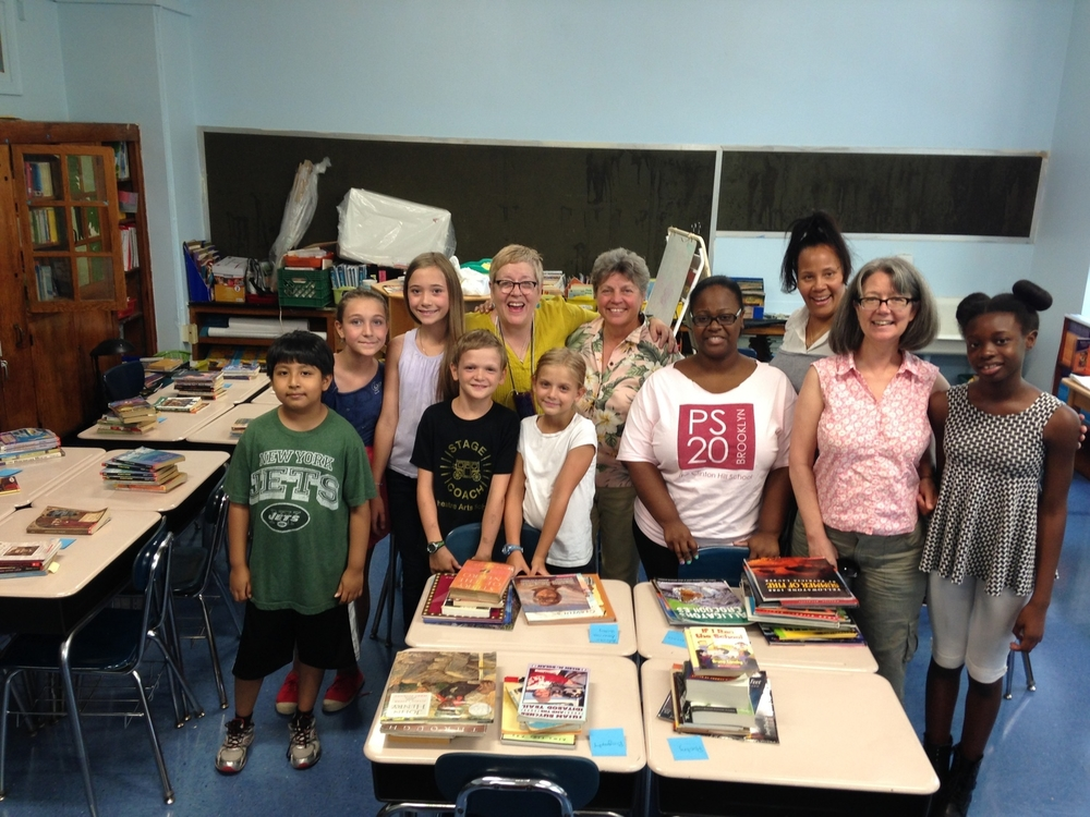 Monica and DK with Kathy Becker in the flowered blouse and Ms. Morrison in (you guessed it) PS 20 tee shirt. Ms. Dixon (the other 5th grade teacher) is behind Monica. The kids helped create a library for the room, among other things.